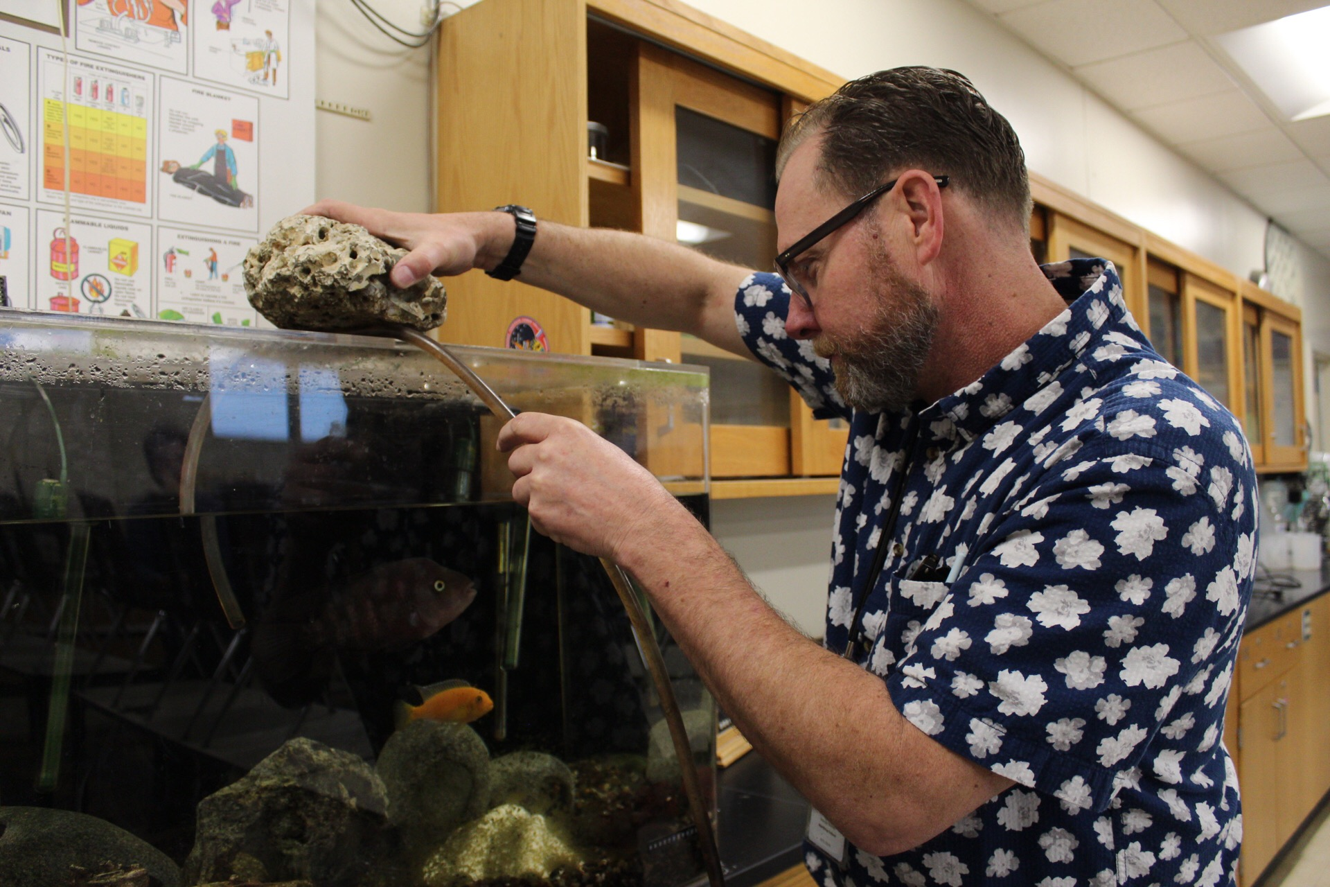 "Former environmental science teacher David Whitman drains his fish tank as he moves out of E210. He currently works as a science teacher at Northrup Elementary. ""I already formed an army of fourth graders at my new job,"" he said. ""They're wonderful kids, really."""