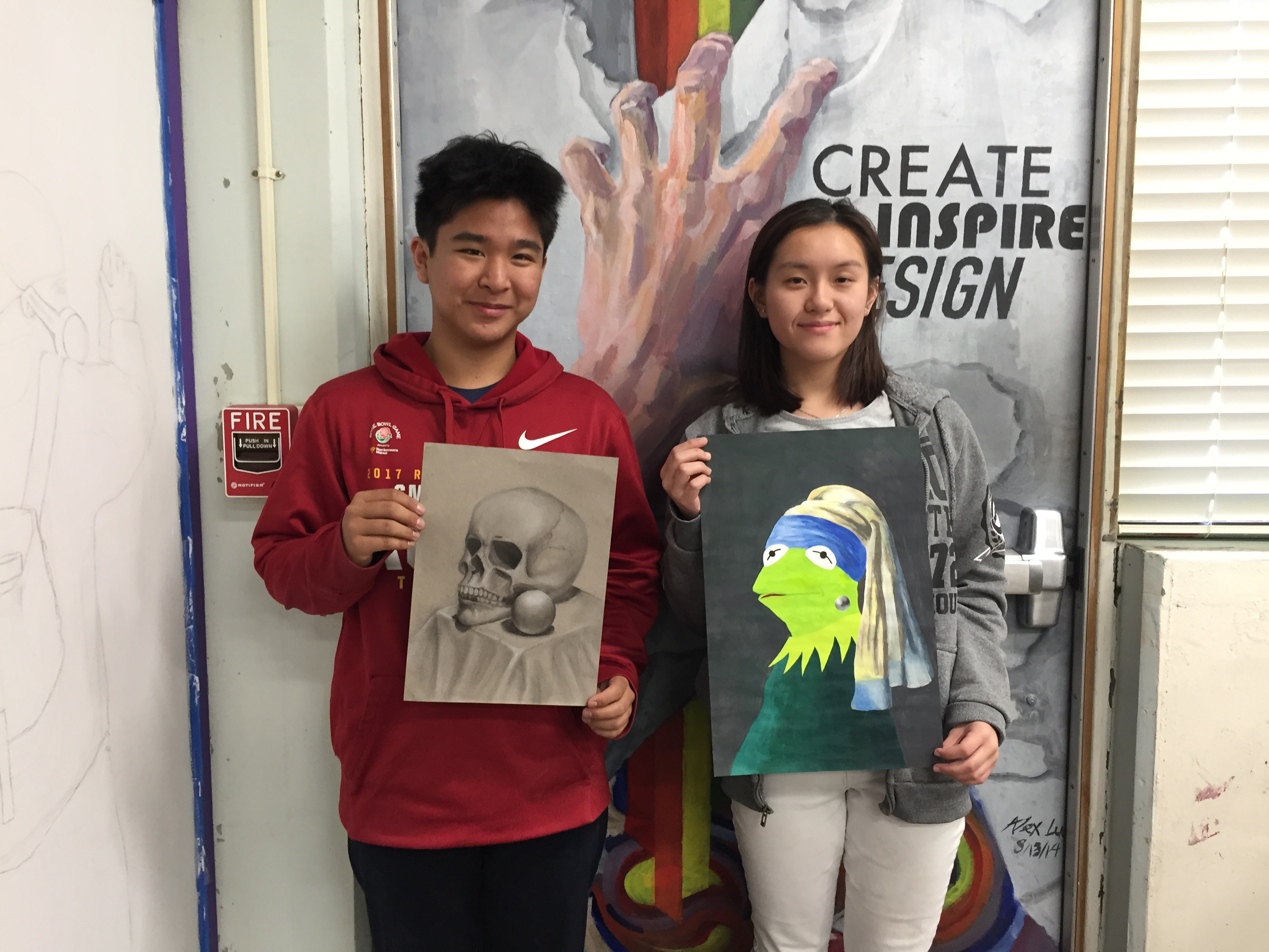 Juniors Joshua Yuan (left) and Ashley Guan (right) stand with their winning pieces during an Art Club meeting, in which the top three voted pieces were announced.